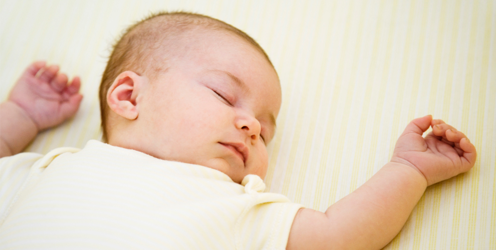 image of baby sleeping on back with hands up.