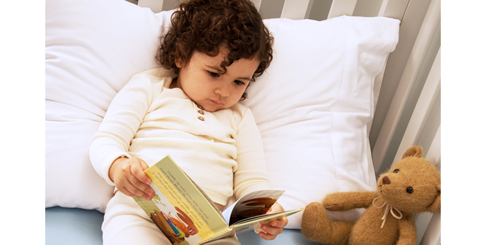 Toddler laying in bed reading a book with teddy bear next to her.
