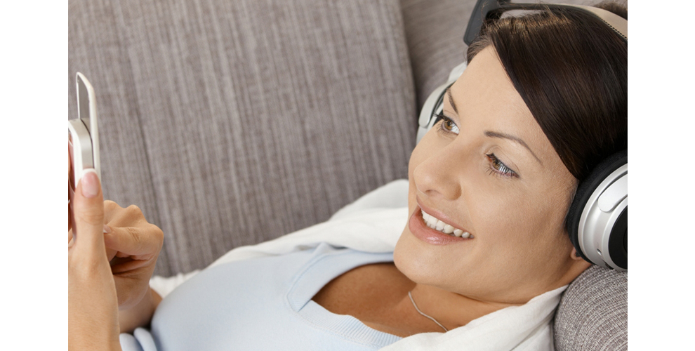 image of women laying on the couch with headphones on listening to podcast on her phone.