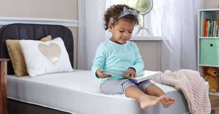 Toddler sitting on a toddler bed and reading