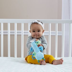 Baby sitting inside crib on crib mattress holding a stuffed toy in hand