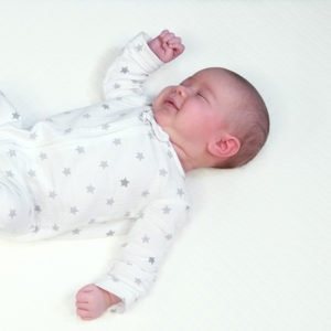 Baby sleeping on their back on a crib mattress