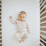 Baby lying on the back on Sealy Posturepedic Grace Crib Mattress