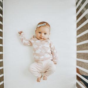 Baby lying on the back on Sealy Posturepedic Grace Crib Mattress